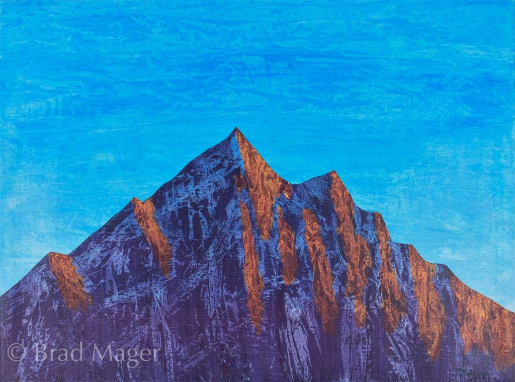 Purple rocky mountain lit with sunrise glow against a blue morning sky