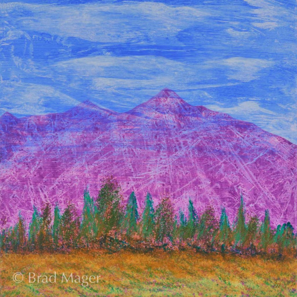 Purple mountains behind a line of trees and a gently-sloping meadow