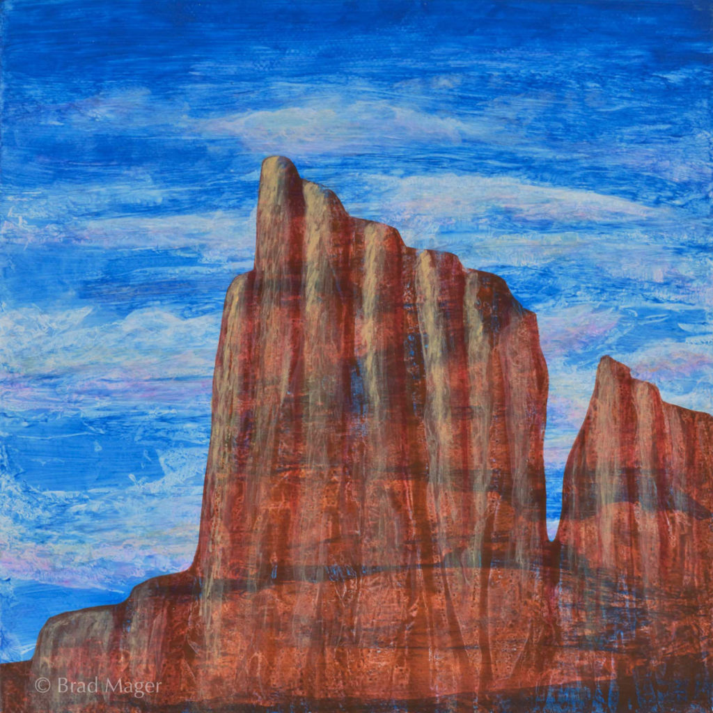 A desert monolith rises against a blue and white cloud sky